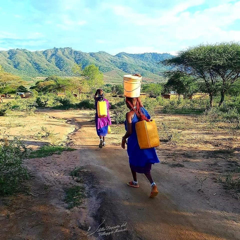 Giovani donne maasai che portano l'acqua
