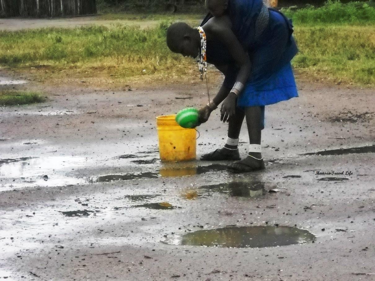 Una giovane mamma maasai raccoglie acqua dalle pozzanghere