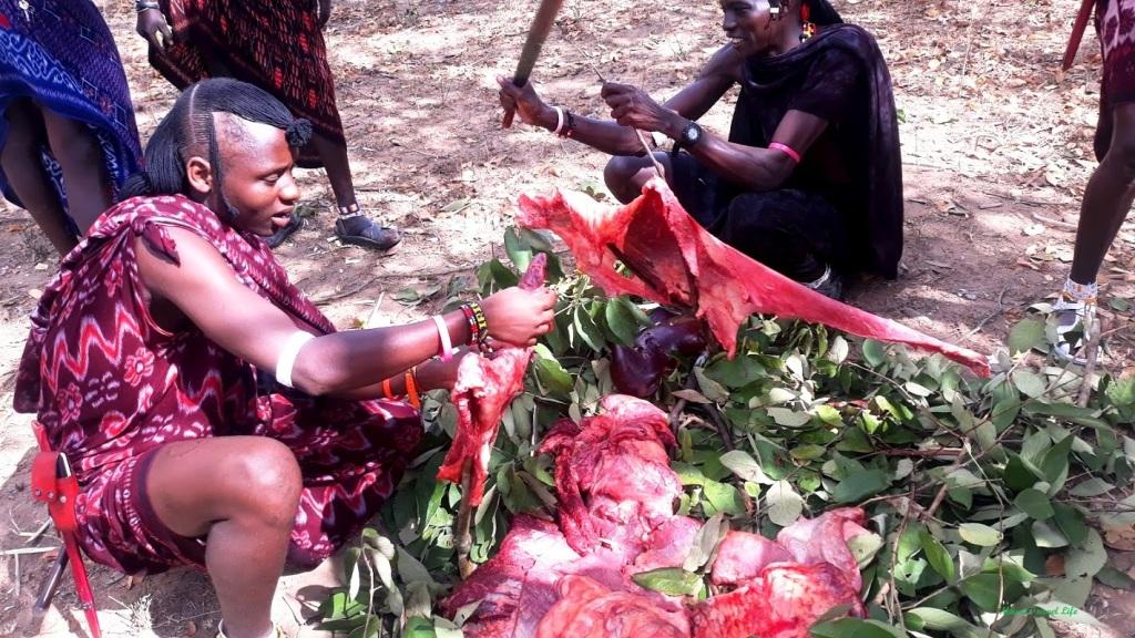 Un gruppo di guerrieri maasai preparano la carne da cucinare